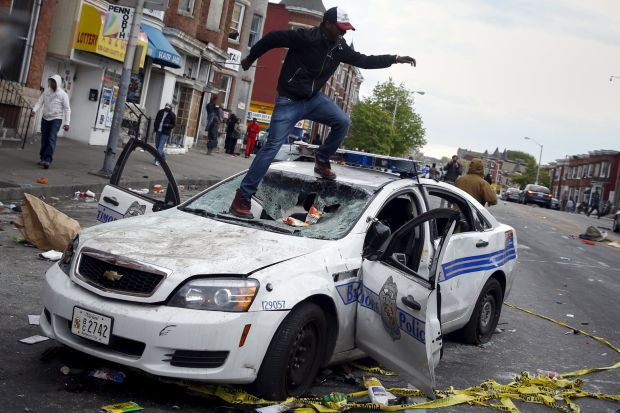 A demonstrator jumps on a damaged Baltimore police vehicle during clashes in the city April 27. Maryland Gov. Larry Hogan declared a state of emergency and activated the National Guard to address the violence after the unexplained death of a 25-year-old black man while in police custody. (CNS photo/Shannon Stapleton, Reuters)