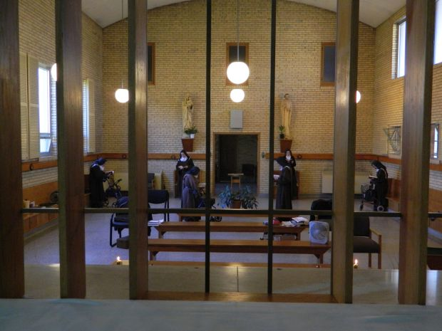 Seen through a divider of wood and metal bars, cloistered nuns sing vespers March 30 in the chapel of the Carmelite Monastery in Louisville, Ky. (CNS photo/Marnie McAllister, The Record)