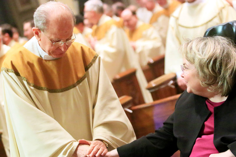 Msgr. Richard Bolger leaves his pew to offer a sign of peace to Sheila Haren from Old St Joes