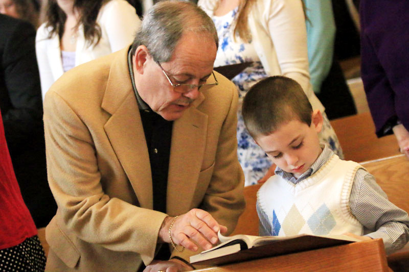 Jim Citro helps his grandson Benjamin find his place in the book