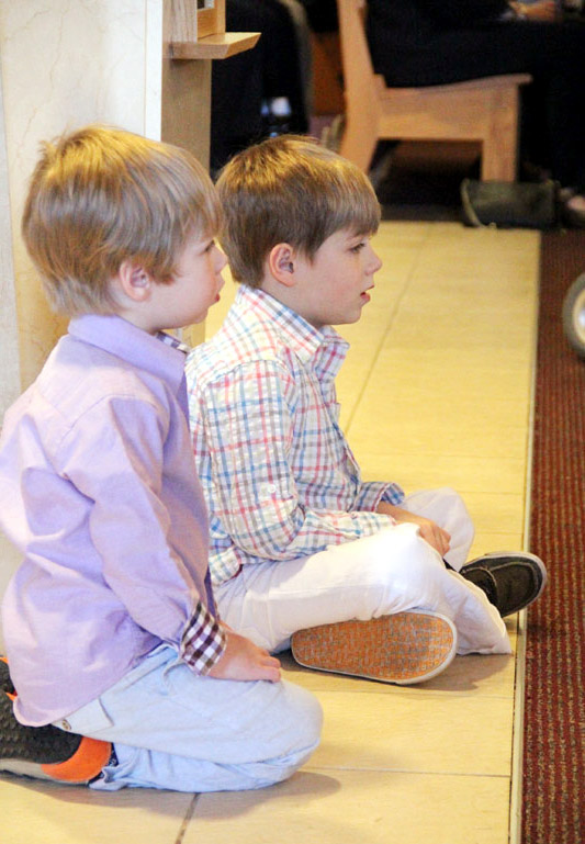 With standing room only brothersConnor and Griffin White take a seat on the floor to listen to Bishop Timothy Seniors homily