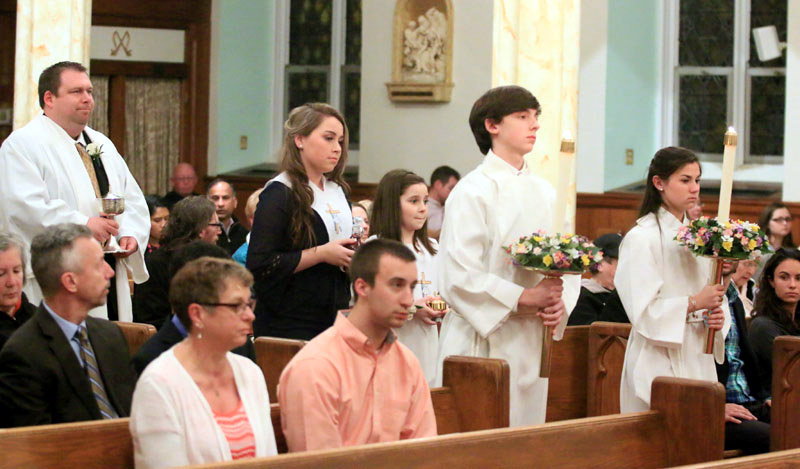 Newly baptized Jard Zangwill, Alexis Devlin and Julianna Devlin bring up the gifts