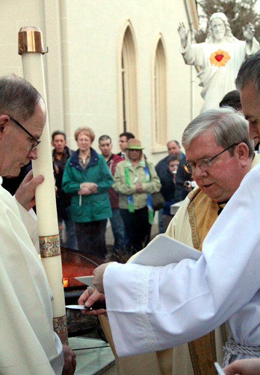 Fr James Lyons carves in the candle