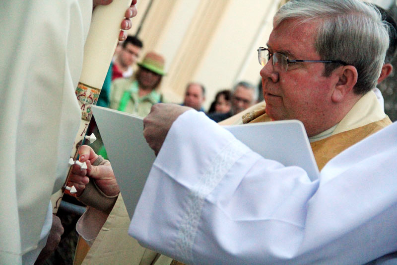 Fr James Lyons puts the pins in the candle