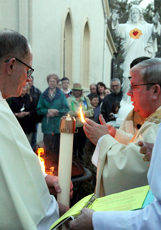 Deacon John Farrell holds the candle as Fr. James Lyons lights it at dusk in the courtyard beside the church