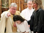 Fr James Lyons baptizes Julianna Devlin with her godparent/sponsor Kathleen Smyth by her side