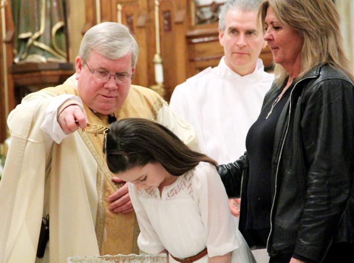 Fr James Lyons baptizes Julianna Devlin with her godparent/sponsor Kathleen Smyth by her side
