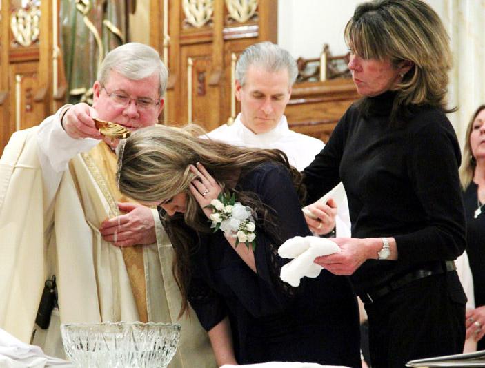 Fr James Lyons baptizes Alexis Devlin with her godparent/sponsor  Doreen Smyth by her side