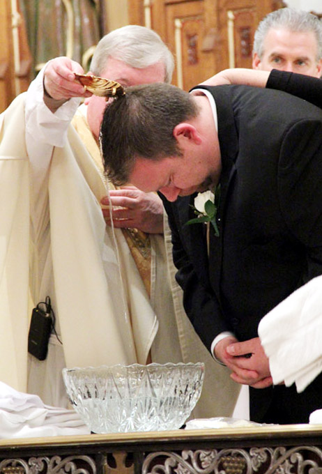Fr James Lyons baptizes Jared Zangwill