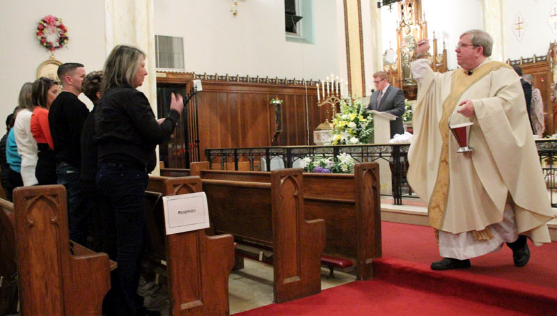 Fr James Lyons sprinkles the people after they renew their baptismal vows