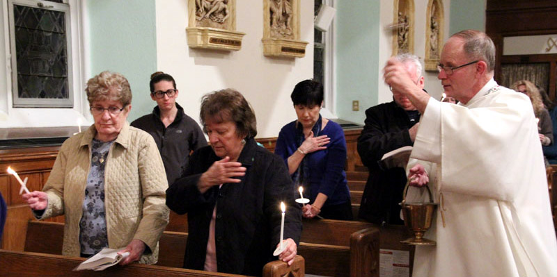 Deacon John Farrell sprinkles the people after they renew their baptismal vows