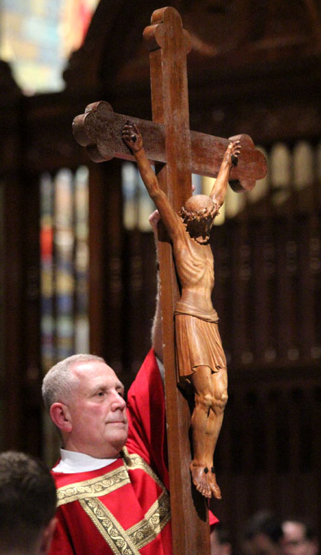 Transitional Deacon James Cordosi holds the cross for veneration during the Good Friday liturgy April 3 at the Cathedral Basilica of SS. Peter and Paul. (Sarah Webb)