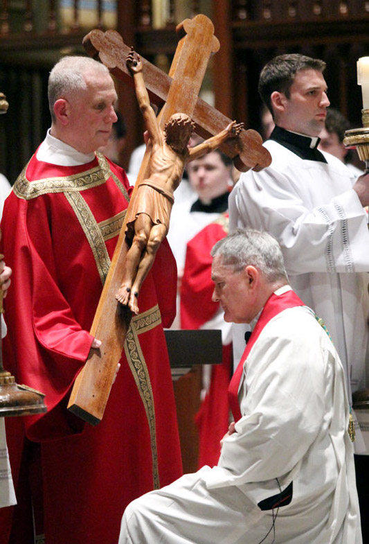 Archbishop Edward Adams venerates the cross held by transitional Deacon James Cordosi April 3 at the Good Friday liturgy at the Cathedral Basilica of SS. Peter and Paul, Philadelphia. (Sarah Webb)