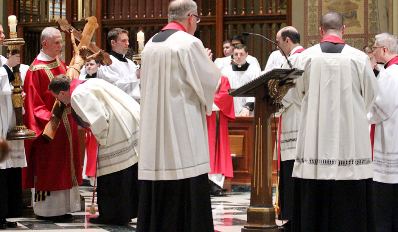 Fr Sean Bransfield venerates the cross along with fellow priests and seminarians