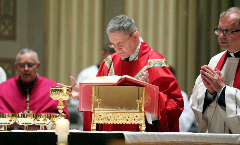Archbishop Edward Adams (center) celebrates the Communion rite during the Good Friday liturgy April 3 at the Cathedral Basilica of SS. Peter and Paul, Philadelphia. With him is Archbishop Charles Chaput, left, and Father Dennis Gill, cathedral rector. (Photo by Sarah Webb)