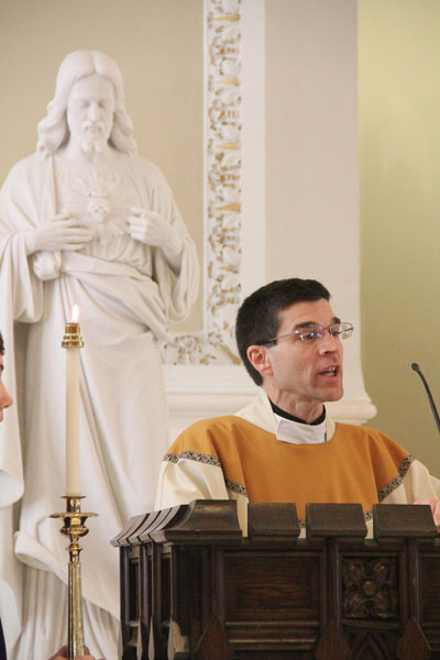 St. Philip Parish's pastor, Father James Oliver, proclaims the Gospel reading during Mass April 19 at the church. (Sarah Webb)
