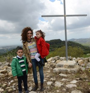 Nijmy Yacoub, 26, stands with her niece and nephew in front of a cross after Easter Monday Mass at St. Mary's Church in Iqrit, Israel, April 13.  (CNS photo/Debbie Hill)