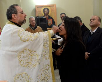 Father Souhail Khoury distributes Communion during Easter Monday Mass at St. Mary's Church in Iqrit, Israel, April 13.  (CNS photo/Debbie Hill)