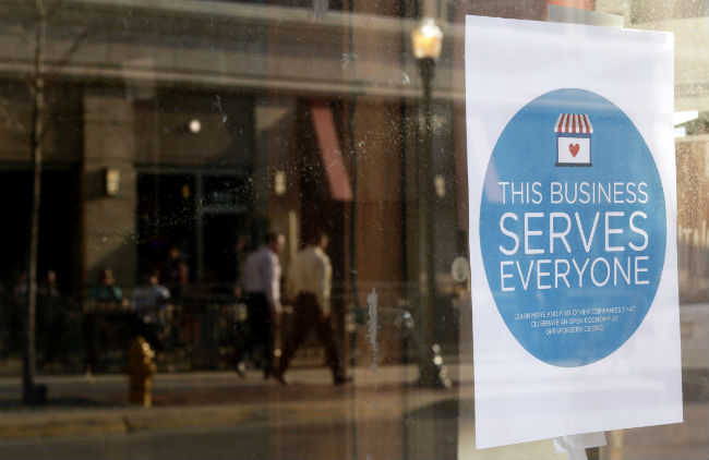 "A sign reading, ""This business serves everyone,"" is seen in the window of a barbershop in downtown Lafayette, Ind., March 31. (CNS photo/Nate Chute, Reuters)"