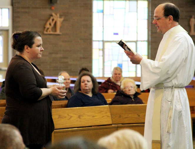 Karen Moylan brings up the oil of the sick before mass to be place in the church