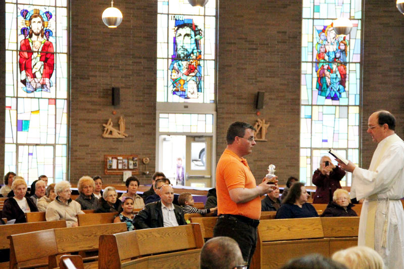 David Moylan brings up the oil of the catechumens before mass to be place in the church