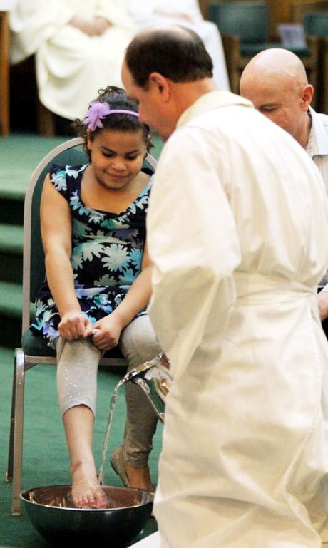 Avonlea Warner gets her feet washes by Fr Thomas Nasta