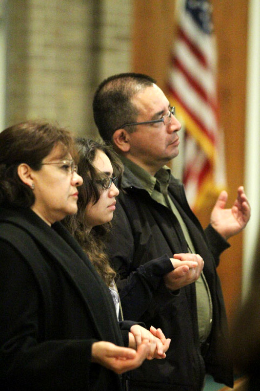 Pilar, Elizabeth and Ed Leyva hold hands as they pray the Lord's Prayer