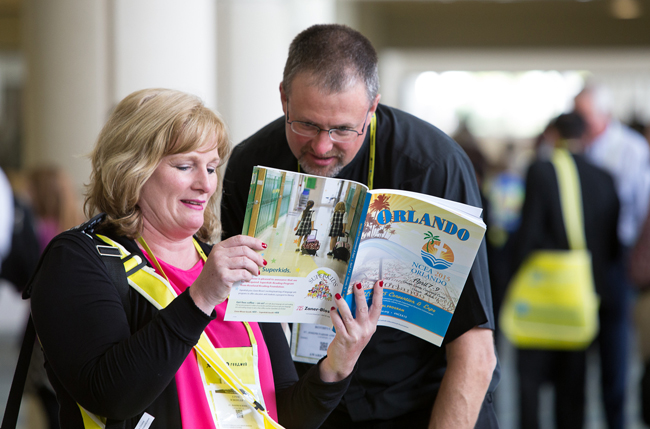 Attendees check the program schedule April 7 during the annual convention of the National Catholic Educational Association held at the Orange County Convention Center in Orlando, Fla. Some 5,000 attendees took part in the three-day event. (CNS photo/Tom Tracy)