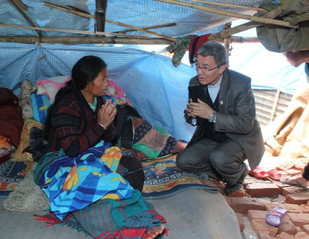 Bishop Paul Simick of Nepal visits an injured Catholic earthquake survivor April 30 in remote Banyatar parish perched on a hilltop overlooking Kathmandu. (CNS photo/Anto Akkara)