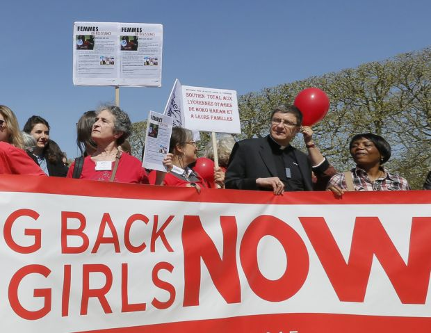"A clergyman joins others in a ""Bring Back Our Girls"" gathering in Paris April 14. A year after more than 200 Nigerian schoolgirls were kidnapped, Lagos Cardinal Anthony Olubunmi Okogie said he believed that ""God will answer our prayers"" for their return. (CNS photo/Gonzalo Fuentes, Reuters)"