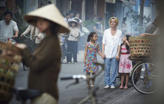 "Deirdre O'Kane, with children, stars in a scene from the movie ""Noble."" The film, which will debut on 150 screens nationwide May 8, tells the story of an Irish woman with an indomitable spirit who years after raising her own children went to Vietnam to help orphans. (CNS photo/Aspiration Media)"