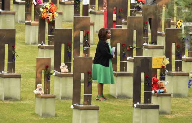 A woman at an April 19 ceremony marking the 20th anniversary of the Oklahoma City bombing stands in the middle of the 168 chairs representing the dead at the Oklahoma City National Memorial & Museum. (CNS photo/Larry W. Smith, EPA)