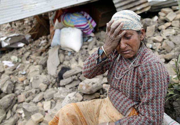 A woman mourns near the body of her 10-year-old daughter outside her destroyed home April 27 on the outskirts of Kathmandu, Nepal. More than 4,300 people were known to have been killed and an estimated 1 million people were left homeless after a magnitud e-7.8 earthquake hit a mountainous region near Kathmandu April 25. (CNS photo/Narendra Shrestha, EPA)