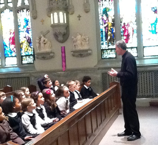 Msgr. Paul Dougherty, pastor of St. Margaret Parish in Narberth, talks to the school's third graders in the church.