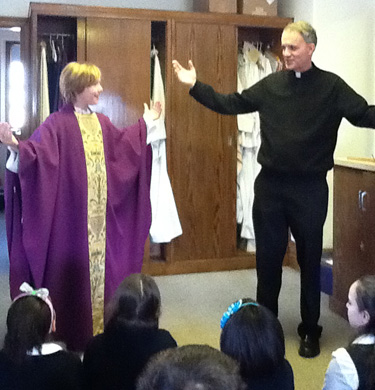 Cormac Rooney, left, shares the excitement with fellow classmates as he dons the vestments of a priest as Msgr. Dougherty discusses aspects of the church and roles of priests.
