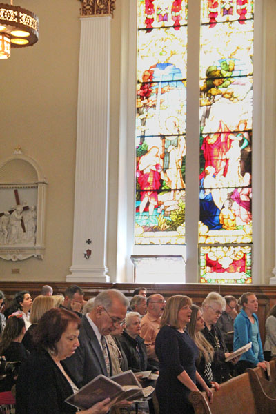 The congregation of young and old pray the liturgy beneath the brilliant windows of St. Philip Church. (Sarah Webb)