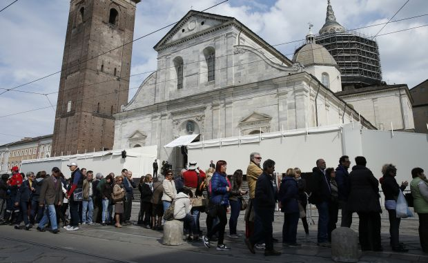 People wait in line outside the Cathedral of St. John the Baptist before the opening of the public exposition of the Shroud of Turin in Turin, Italy, April 19. (CNS photo/Paul Haring)2015.