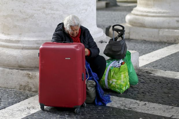A homeless woman sits with her belongings as she waits for a friend leaving the Vatican following a March 26 visit. For an upcoming Vatican charity concert, Rome's immigrants, poor, elderly and marginalized will be getting front-row VIP treatment, while benefactors will be seated in the back. (CNS photo/Max Rossi, Reuters)