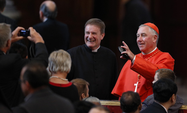 New Cardinal John Dew of Wellington, New Zealand, greets guests as he arrives for a Mass with Pope Francis and new cardinals in St. Peter's Basilica at the Vatican Feb. 15. The Cardinal was among those giving curia assignments by the pope April 13. (CNS photo/Paul Haring)