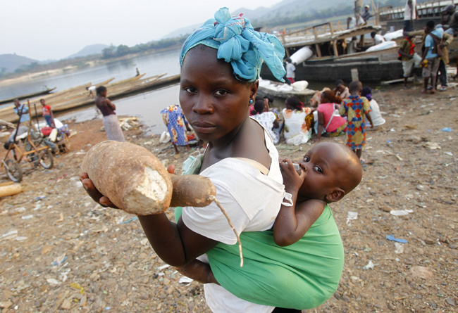 A woman sells cassava on the banks of the Ubangi River near the border between the Central African Republic and the Democratic Republic of Congo, where violence has intensified. (CNS photo/Legnan Koula, EPA)