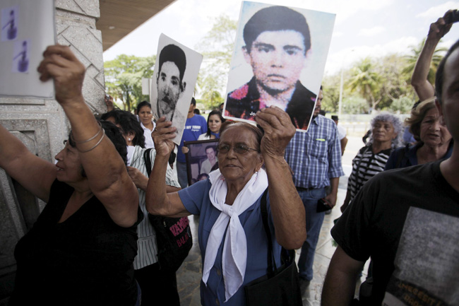 Relatives of war victims protest against retired Gen. Carlos Eugenio Vides Casanova, a former director of the Salvadoran national guard, upon his arrival at El Salvador International Airport April 8. Casanova was deported from the United States for his alleged involvement in torture and killings during the 1979 to 1992 civil war in El Salvador. (CNS /Jose Cabezas, Reuters)