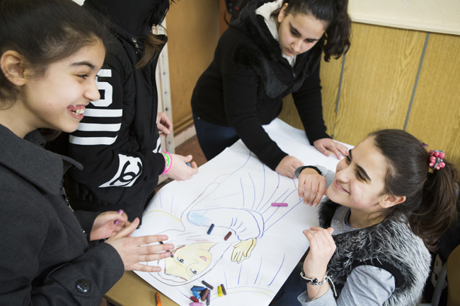 Girls smile during art class March 25 at Don Bosco youth center in Istanbul. (CNS photo/Elie Gardner)
