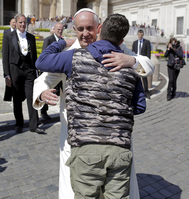 Pope Francis embraces a man at the end of his weekly audience in St. Peter's Square at the Vatican April 8. (CNS photo/Tony Gentile, Reuters)