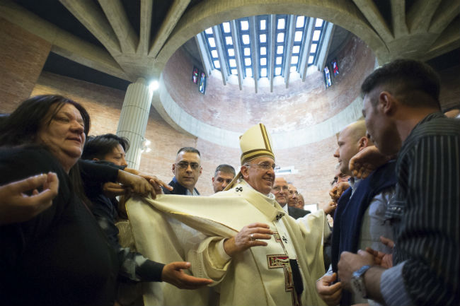 People tug at Pope Francis' vestments as he meets inmates at Rome's Rebibbia prison on Holy Thursday, April 2. (CNS photo/L'Osservatore Romano via Reuters)