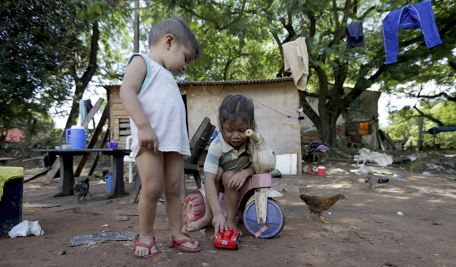 Children play outside their house March 31 in a slum in Asuncion, Paraguay. The World Bank and global faith leaders are joining together to end extreme poverty around the world by 2030. (CNS photo/Jorge Adorno, Reuters)