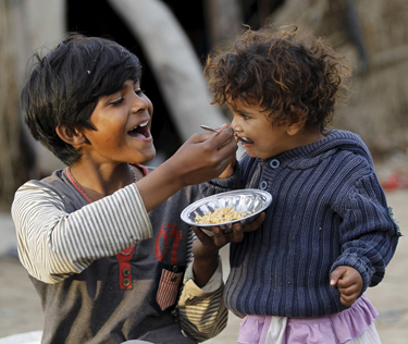 A boy feeds his sister in a slum on the outskirts of Islamabad March 30. (CNS photo/Caren Firouz, Reuters)