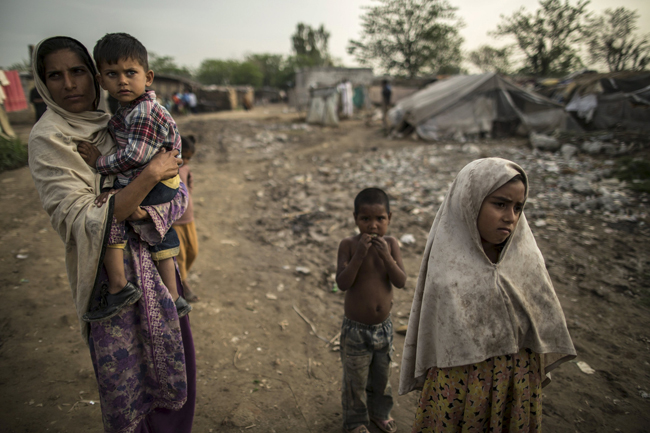 A woman carries her son as they watch children playing on a swing at a slum on the outskirts of Islamabad March 30.  (CNS photo/Zohra Bensemra, Reuters)