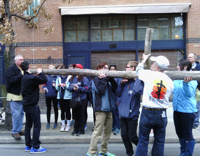 Local teenagers and their adult helpers hoist a cross for a procession and prayerful public witness called CrossWalk in which they carried the cross through the streets of center city Philadelphia on Good Friday, April 3.