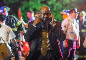 Philadelphia Mayor Michael Nutter speaks on a cellphone as emergency responders search for passengers following an Amtrak train derailment in Philadelphia May 12.  (CNS photo/Bryan Woolston, Reuters)