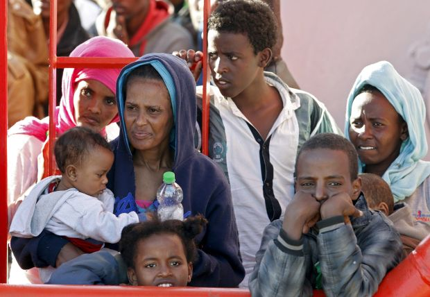 Migrants wait to disembark from a tug boat in the Sicilian harbor of Pozzallo May 4. More than 3,600 migrants were rescued at sea in 17 different operations in just one day in early May, according to the Italian coast guard. (CNS photo/Antonio Parrinello, Reuters)